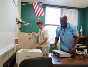 Derek Hastings, a rising senior at Wando HS, is assisting with the reconnection of hardware in classrooms at his school in preparation for the upcoming school year.